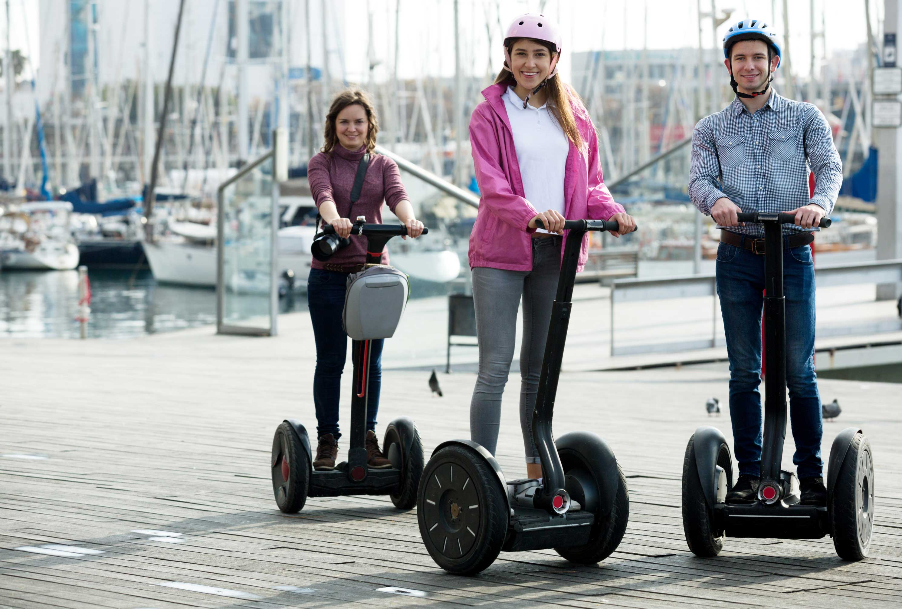 photodune-16501874-girls-and-guy-traveling-through-city-by-segways-l